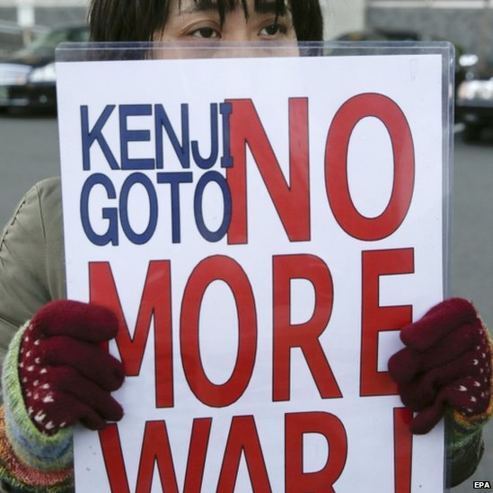 A protester holds a placard outside PM Abe's residence in Tokyo. Photo: 1 February 2015