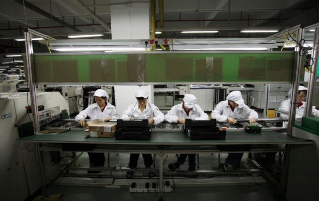 Workers are seen inside a Foxconn factory in the township of Longhua in the southern Guangdong province. The firm is believed to be installing thousands of robots to help build Apple's latest iPhone.