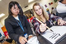 Nao Murakami, a student from Takata High School in Japan, teaches Japanese calligraphy to freshman Brook Nolan at Del Norte High School on Tuesday. Nao was one of 14 Takata High School students visiting Del Norte County this week. Del Norte Triplicate / Bryant Anderson